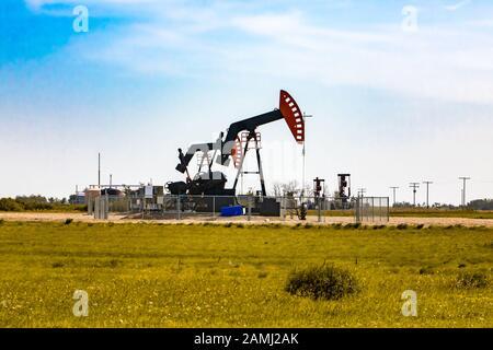 Eine Weitwinkelansicht von zwei geschlossenen Ölquellen mit oberirdischen Pumpenkästen und Arbeitszahnrad. Umgeben von ländlichen Farmen in Saskatchewan, Kanada. Mit Kopierbereich - Stockfoto