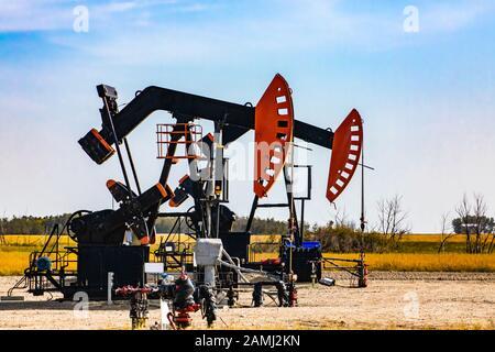 Details zu zwei Ölquellen im ländlichen Kanada. Aka Nicken von Pferden, Eseln, Pumpen. Gegengewicht und Kurbel mit Gehbalken. Endlicher Ressourcenabbau - Stockfoto