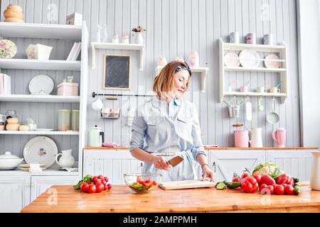 Schöne junge Frau bereitet Gemüsesalat in der Küche zu. Gesunde Ernährung. Kochen zu Hause. Diät-Konzept. - Stockfoto