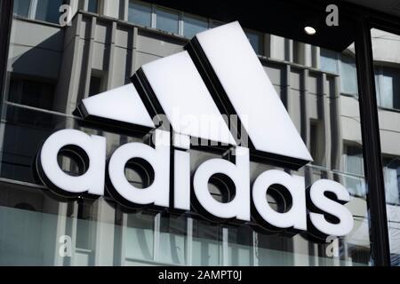 Das Schild von adidasauf dem Fensterschweller aus Glas aufgehängt. Nahaufnahme. Das Foto wurde kontrastreich aufgenommen. Tabelle schreibt den Namen und das Logo von Adidas in Schwarzweiß. - Stockfoto