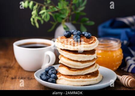 Pfannkuchen mit Blaubeeren und Honig. Stapel leckerer Buttermilchpfannkuchen. Horizontale Zusammensetzung, Frühstück