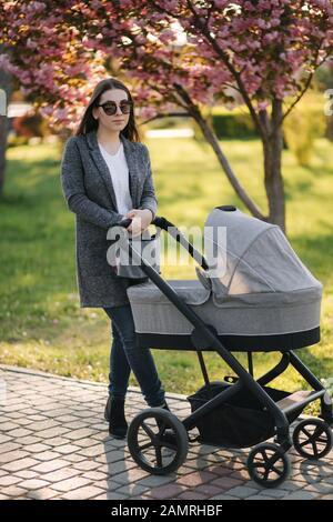 Portrait von Mama mit Kinderwagen im Park. Glückliche junge Mutter mit Baby. Hintergrund der rosa Baum - Stockfoto