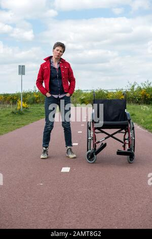 Frau mit Multipler Sklerose im Freien neben ihrem Rollstuhl, Tilburg-Reeshof, Noord-brabant, Niederlande - Stockfoto