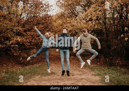 Drei Kinder in einem Herbstwald springen in die Luft, Niederlande - Stockfoto