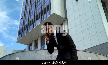 Extrem ärgerlicher mulatto Geschäftsmann, der telefoniert, überarbeiteter Mitarbeiter - Stockfoto