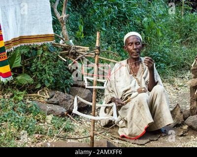 Der äthiopische Mann spinnt Schafhaar außerhalb des Dorfes, Bahir dar, Äthiopien. - Stockfoto