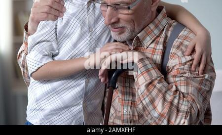 Liebevoller Enkel, der Großvater, Pflege und Unterstützung älterer Generationen umfasst - Stockfoto