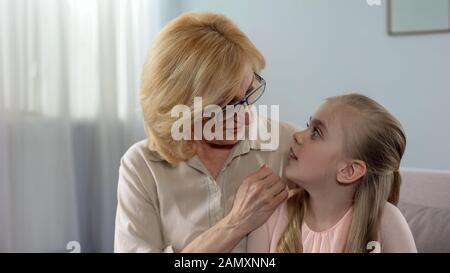 Lächelnde Großmutter flüstert ihrer schockierten Enkelin, Familie, geheim - Stockfoto