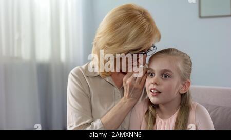 Großmutter flüstert ihrem Enkeltochter, Unterhaltungen der Frauen, das größte Geheimnis - Stockfoto