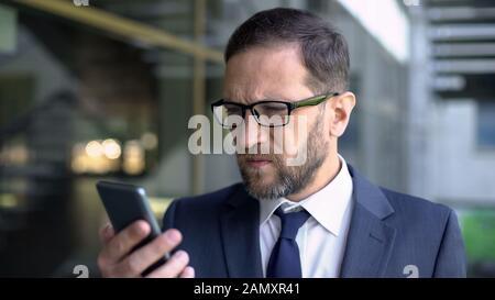 Manager in Brillen, die versuchen, Smartphone-Nachrichten zu lesen, schlechtes Sehvermögen, Gesundheitspflege - Stockfoto