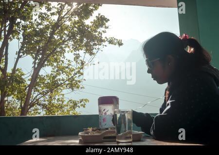 Frau, Essen, Frühstück, während er auf dem Esstisch in Morgen bei holiday home gegen Himalaya Berge im Hintergrund. - Stockfoto