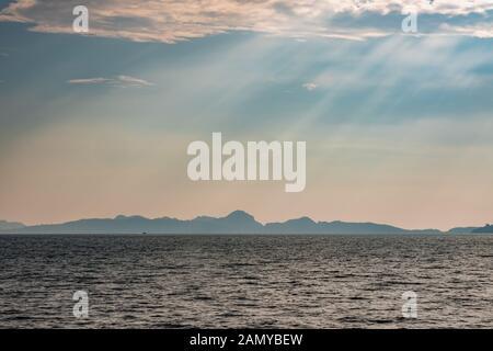 Dramatische Sonnenstrahlen auf dem Meer vor der Küste von Thailand. Hügel von Phi Phi Island kann im Hintergrund gesehen werden. - Stockfoto