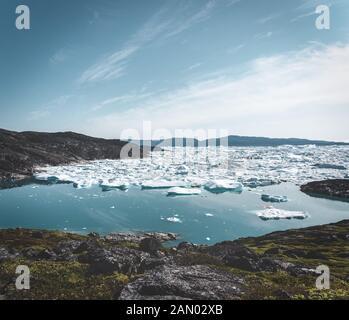 Wunderschöne Landschaft mit schwimmenden Eisbergen in der Gletscherlagune und dem See in Grönland. Ilulissat Icefjord-Gletscher. Eisberg und Eis vom Gletscher in Stockfoto
