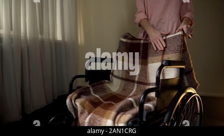 Tochter streichelt leeren Rollstuhl mit Trauer, erinnert sich Mutter - Stockfoto