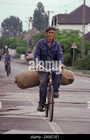 Ein ungarischer Mann ist am 18. Juni 1990 in Ungarn mit einem großen Sack an Produkten in einem Dorf im ländlichen Ungarn unterwegs. - Stockfoto