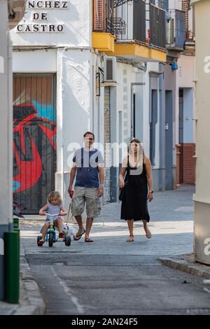 Eltern folgen geduldig einem kleinen Mädchen, das in einer ruhigen Straße in Sevilla auf ihrem Trike reitet
