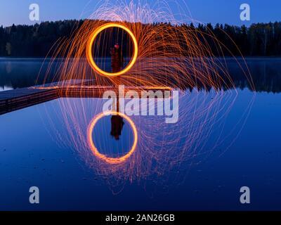 Brennende Stahl Wolle spinnen, Duschen glühende Funken von spinning Stahlwolle, schöne Spiegelungen im Wasser - Stockfoto
