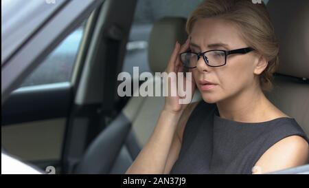 Business Frau im Auto sitzen und leiden unter starken Kopfschmerzen, Migräne - Stockfoto