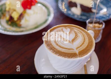 Eine Tasse Cappuccino oder Latte mit Blumenmuster aus Latte Art in weißem Becher auf Holztisch. Hiphster vibes und Vintage-Ton. - Stockfoto