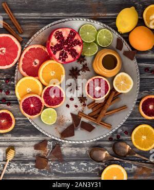 Top down Sicht auf eine abstrakte Collage von Zitrusfrüchten zusammen mit Zimt, Honig und Schokolade. Stockfoto