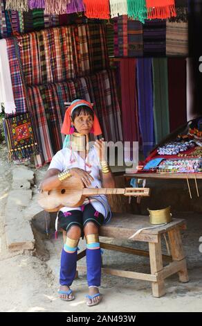 Eine Padaung Frau spielen ein traditionelles Saiteninstrument. Stockfoto