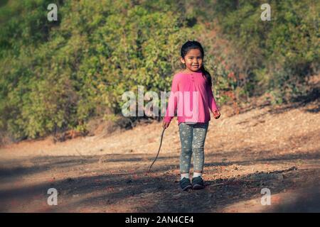 Junge Mädchen tragen rosa shirt Wer ist zu Fuß, indem Sie sich auf einem Wanderweg beim Halten eines hölzernen Stock in der Hand. - Stockfoto
