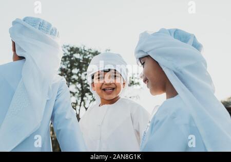 Kinder spielen zusammen in Dubai im Park. Gruppe von Kindern, die traditionelle kandura weißes Kleid aus arabischen Emirate - Stockfoto