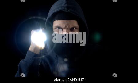 Gesetzesübertreter in Balaclava mask blinkende Taschenlampe, Suchen nach wichtigen Informationen - Stockfoto