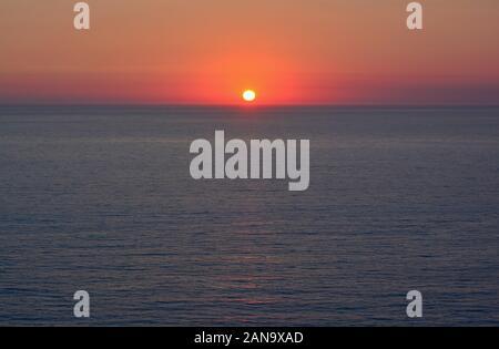 Sonnenuntergang über dem Meer, rot brennenden klarer Himmel, Horizont und dunklen, blauen Meer Oberfläche - Stockfoto