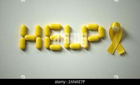 Weibliche Inverkehrbringen gelbe Band, Hilfe Wort von Pillen auf Tisch, Krebs im Kindesalter - Stockfoto