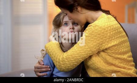 Mutter umarmt traurigen kleinen liebenswerten Mädchen nach Hause nach Arbeit, Familie Liebe und Fürsorge - Stockfoto