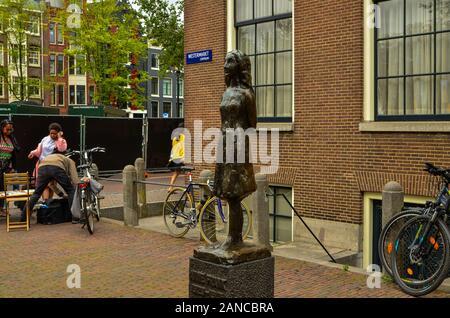 Amsterdam, Holland, August 2019. Die Statue von Anne Frank ist ein Reiseziel für viele Touristen: Viele posieren für ein Erinnerungsfoto mit ihr. Es befindet sich b - Stockfoto