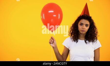 Lonely afrikanische Frau mit roten Ballons, traurig auf Geburtstagsfeier - Stockfoto