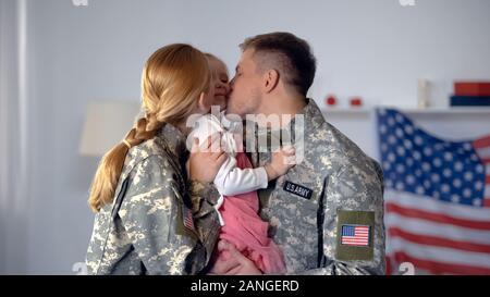 Fröhliche militärischen Paar küssen kleine Kind in Wangen, USA-Flagge im Hintergrund - Stockfoto