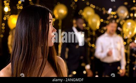 Unglücklich asiatische Frau, tanzende Menschen in night club suchen, Langeweile - Stockfoto