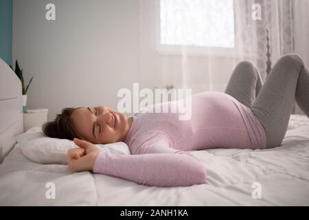 Schwangere Frau schläft und Stretching in ihrem Bett.