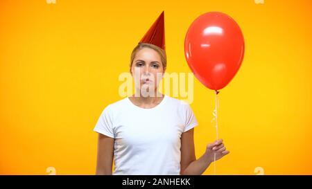 Frau mit roten Ballon in der Hand aufgebracht, einsam auf der Geburtstagsparty, Trauer - Stockfoto
