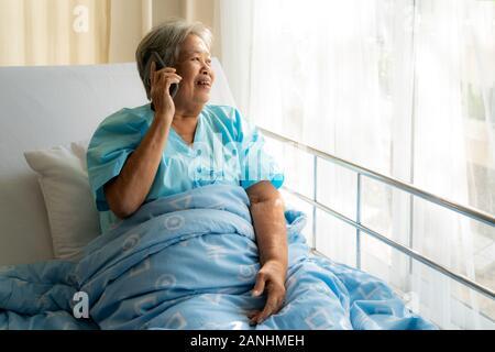 Asiatische senior Senioren mit Chats zu Familie auf Ihrem Mobiltelefon und lächelnd, mit Freude, als sie das Gespräch hört, während Sie Krankheit in Ho - Stockfoto