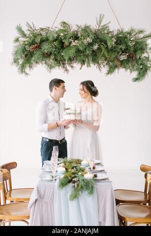 Braut und Bräutigam die Hochzeitstorte genießen Sie Mahlzeiten im Hochzeit mit Pinien und Kerzen - Stockfoto