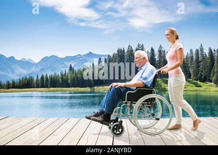 Junge Frau bei Ihrem deaktivieren Großvater im Rollstuhl zu Fuß auf der Promenade in der Nähe des Sees - Stockfoto