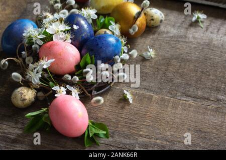 Bunte Ostereier im Nest mit Weidenruten und Frühlingsblumen auf grauem Hintergrund aus Holz. Kopieren Sie Platz. - Stockfoto