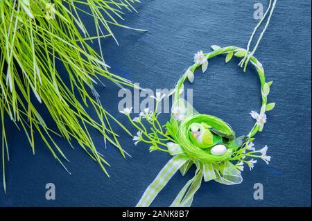 Frühjahr Zusammensetzung mit einer geflochtenen Kranz aus Zweigen mit Kirschblüten, dekorative Vogel und Osterei auf einem klassischen blauen einfachen Hintergrund. Kopie der - Stockfoto