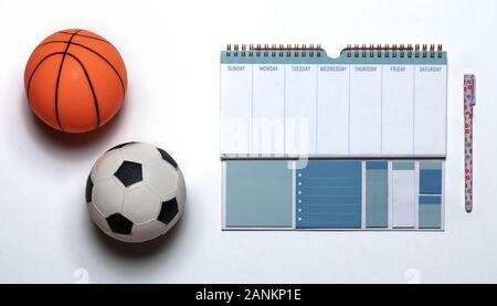 Kleine Gummi Spielzeug Basketball und Fußball mit einem Workout Plan auf weißem Hintergrund. Flach, kopieren. - Stockfoto