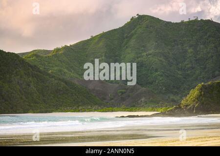 Atemberaubende Aussicht auf die selong Belanak Strand durch eine grüne bergige Küste bei Sonnenuntergang flankiert. - Stockfoto