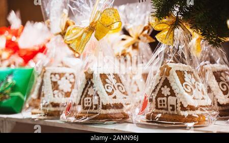 """Weihnachten handgemachte Lebkuchenplätzchen auf Holzregal, kleiner hausförmiger Kuchen, mit rotem und goldenem Bogen, eckige Plätzchen mit Stadt """"Krakow"""" (Crac - Stockfoto"""