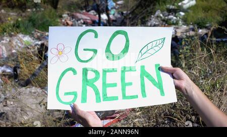 Grüne Phrase auf Pappe in Person die Hände gegen offene Dumping Hintergrund gehen - Stockfoto