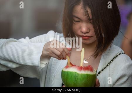 Feng Huang, China - August 2019: Chinesisches Mädchen essen Stücke schneiden Sie die köstlichen und reife Wassermelone auf der Straße in der Altstadt in Feng Huang, Huna - Stockfoto
