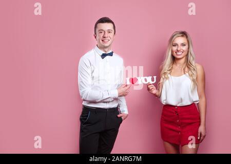 Ich liebe Dich. Glückliches Paar in der Liebe auf rosa Hintergrund - Stockfoto