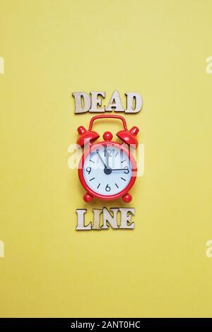 Holz- Briefe mit einer Uhr rot auf gelbem Hintergrund. Konzept Dead line. Ansicht von oben. Close Up. - Stockfoto
