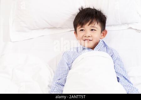 Fünf Jahre altes Kind im Bett liegt im Krankenhaus suchen glücklich - Stockfoto